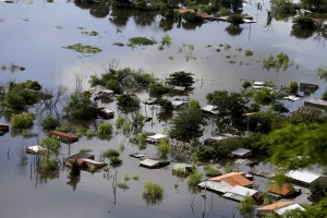 Houses are partially submerged in floodwaters in Asuncion, December 20, 2015. The National Emergency Secretary estimates that about 65,000 people are affected by the flooding of the country's two main rivers, the Paraguay and the Parana. REUTERS/Jorge Adorno - RTX1ZIPP